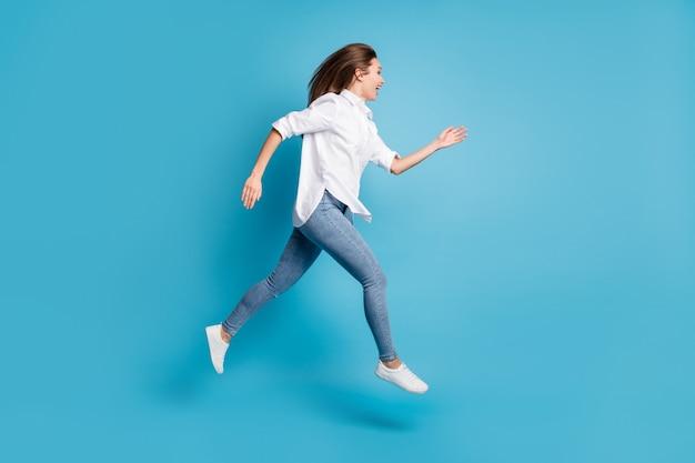 Profielfoto van de volledige lengte van een dame die hoog springt, draagt een wit overhemd, jeans, schoenen, geïsoleerde blauwe achtergrondkleur