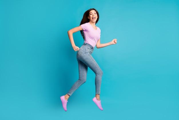 Profielfoto van de volledige lengte van een funky mooi meisje dat springt met open mond, roze t-shirt, schoeisel, spijkerbroek, geïsoleerde blauwe kleurachtergrond draagt