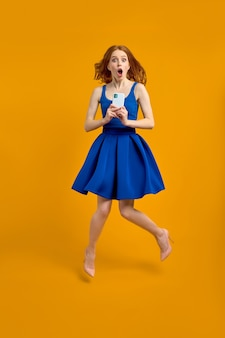 Profielfoto van de volledige lengte van een geschokte roodharige dame die hoog springt met telefoon, lees shockblogcommentaar draagt lente zomer blauwe jurk geïsoleerde gele kleur achtergrond. portret