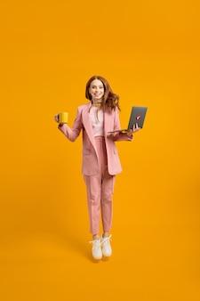 Profielfoto van de volledige lengte van grappige zakendame hoog springen, laptop vasthouden en kopje koffie in handen verslaafde werknemer altijd online dragen roze pak outfit, witte sneakers, geïsoleerde gele achtergrond