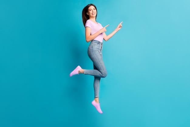 Profielfoto van de volledige lengte van meisje springen directe vingers lege ruimte draag roze t-shirt sneakers jeans geïsoleerd blauwe kleur achtergrond