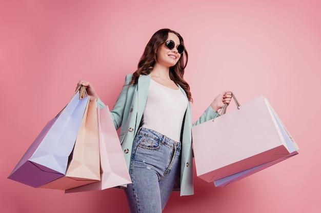 Profielfoto van een jonge brunette vrouw die met boodschappentassen loopt en modieuze kleding op een roze muur draagt
