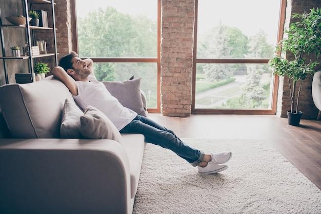 Profielfoto van een man van gemengd ras, zittend op een gezellige bank, hand in hand achter het hoofd ontspannen, huiselijk weekend humeur, zoek dromerig nieuwe reparatie slijtage casual outfit platte zolder woonkamer binnenshuis