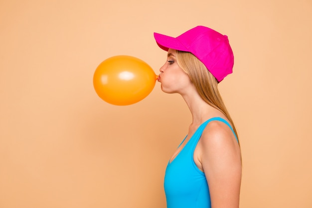 Profielfoto van funky meisje dat gele luchtballon blaast
