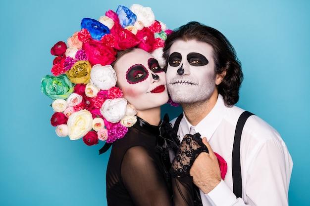 Profielfoto van griezelig romantisch koppel man dame meisje hand in hand wang-tot-wang poseren voel genegenheid dragen zwarte jurk dood kostuum rozen hoofdband bretels geïsoleerde blauwe kleur achtergrond