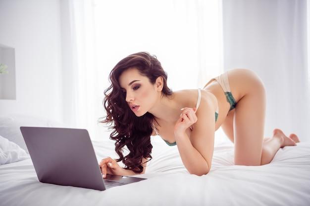 Profielfoto van hete ondeugende dame thuis werk op afstand online chat uitkleden show schrijven klant sms klaar opstijgen beha voor geld staan knieën kat pose draag bikini lakens slaapkamer binnenshuis