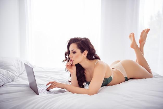Profielfoto van hot home remote worker lady quarantaine online laptop chat klaar uitkleden kijk scherm fit lichaam voor geld schrijven vip klant sms dragen bikini liggend linnen slaapkamer binnenshuis