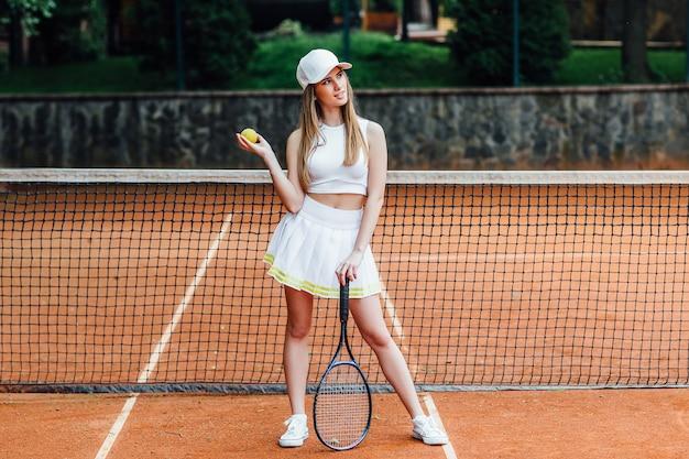 Profielfoto van jonge gelukkige vrouw in sportkleding, tennissen, wachten op de service.