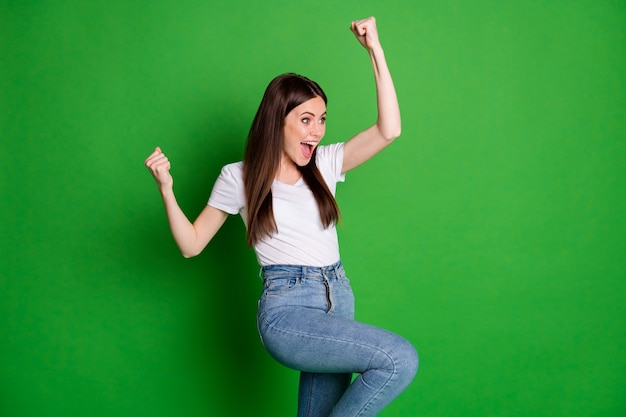 Profielfoto van lief schattig meisje draagt casual outfit vieren winnaar armen omhoog open mond geïsoleerde groene kleur achtergrond