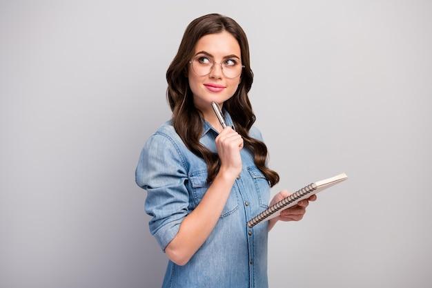 Profielfoto van mooie freelancer dame houd persoonlijke planner minded slimme creatieve persoon pen op kin slijtage specs casual jeans denim overhemd geïsoleerde grijze kleur