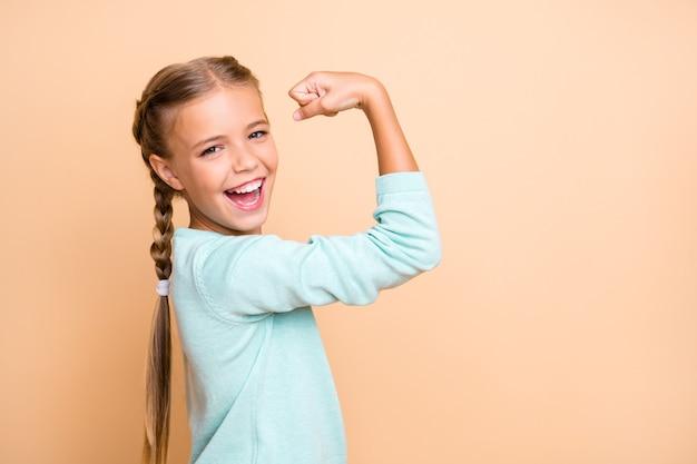 Profielfoto van mooie opgewonden kleine dame ambitieuze persoon steekt vuist op en viert een succesvolle training, draagt ?? blauwe trui, geïsoleerde beige pastelkleurige muur