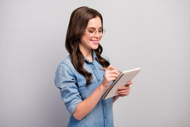 Profielfoto van mooie student dame houd persoonlijke planner opmerken lezing leren studie informatie slijtage specs casual jeans denim overhemd geïsoleerde grijze kleur