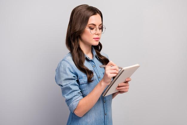 Profielfoto van mooie zakelijke dame houd persoonlijke planner nota baas informatie slijtage specs casual jeans denim overhemd geïsoleerde grijze kleur