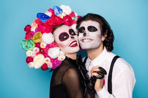 Profielfoto van schattig eng romantisch koppel man dame hand in hand knuffelen wangen stralend glimlachen dragen zwarte jurk dood kostuum rozen hoofdband bretels geïsoleerde blauwe kleur achtergrond