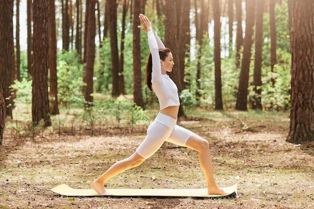 Profielfoto van sportieve vrouw in witte stijlvolle top en leggins, staand in yoga-positie, recht vooruit kijkend, armen omhoog, trainend op karemat in bos, genietend van frisse lucht.