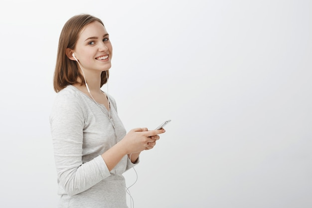 Profielfoto van vermaakte, goed uitziende, zorgeloze volwassen vrouw met kort bruin kapsel die smartphone opzij houdt met tevreden schattige glimlach, muziek luistert in oortelefoons over grijze muur