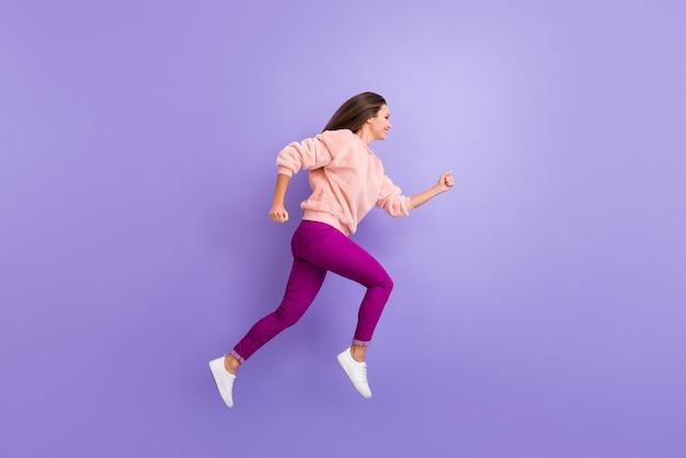 Profielfoto van volledige lengte van actieve dame die hoog op haastige snelheid springt