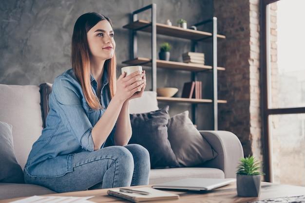 Profielkant van een mooi tevreden mooi meisje zit een comfortabele divan met een cappuccinokopje