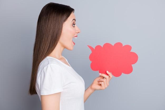 Profielkant verbaasd positief meisje houdt rode papieren kaart wolkschreeuw vast