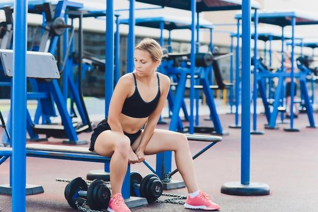 Profielmening van vrouwelijke atleet die sommige triceponderdompelingen op parkbank doen.