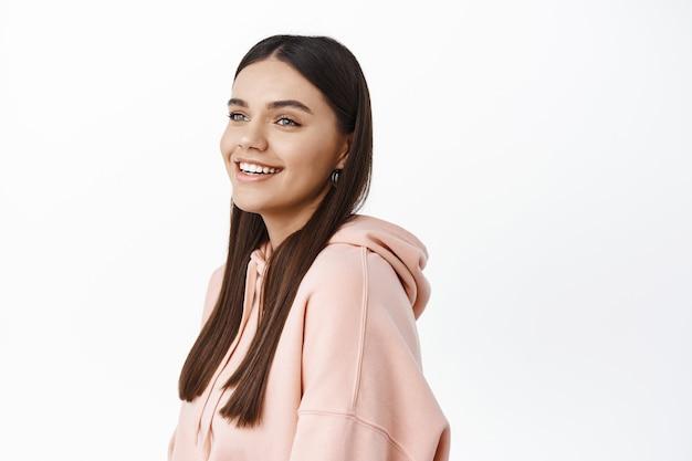 Profielopname van een glimlachende jonge vrouw die gelukkig kijkt naar de kopieerruimte aan de linkerkant, een roze hoodie draagt en tegen een witte muur staat