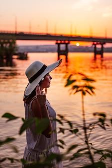 Profielportret van een charmant meisje dat haar handen vasthoudt bij de rand van een strohoed op een rivierstrand met...