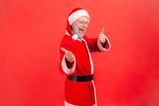 Profielportret van een oudere man met een grijze baard die een kerstmankostuum draagt en naar de camera kijkt met een opgewonden blik, knipoogt en duim omhoog laat zien. indoor studio opname geïsoleerd op rode achtergrond.