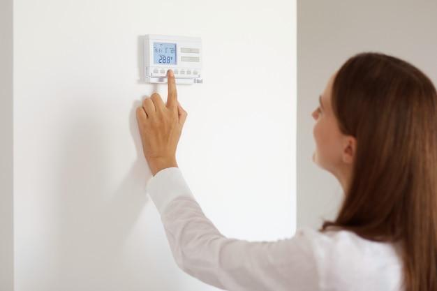 Profielportret van een vrouw met donker haar in een wit casual stijlshirt dat de temperatuur op de thermostaat aanpast, op knoppen drukt, poserend in een lichte kamer thuis.