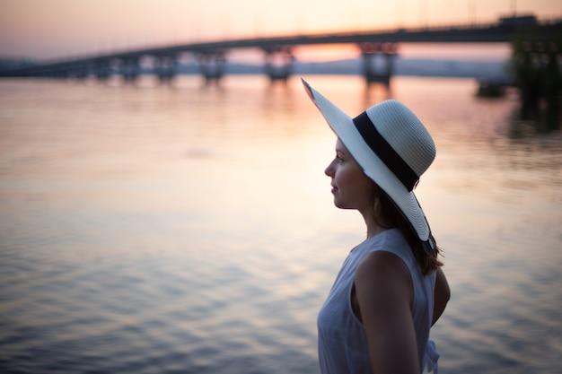 Profielportret van een vrouw met een hoed op een minitrip langs de rivier bij zonsondergang