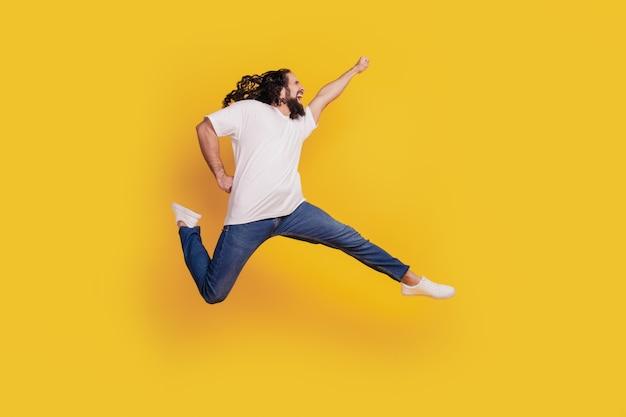 Profielportret van geïnspireerde positieve gekke kerel rent snel springheld verplaatsen op gele achtergrond