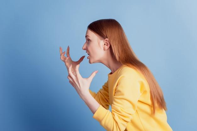 Profielportret van geïrriteerde gekke ontevreden dame kijk lege ruimte, steek handen pms concept op blauwe achtergrond op