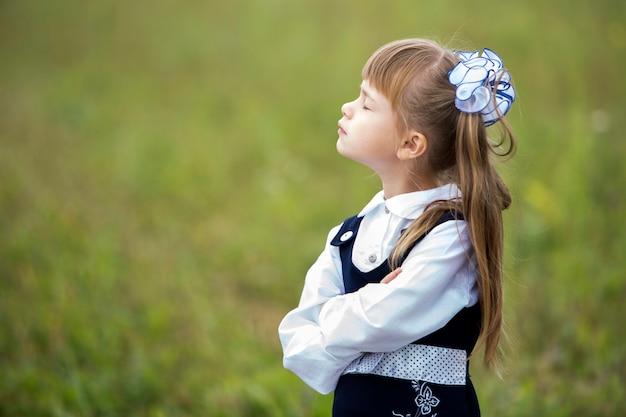 Profielportret van leuk aanbiddelijk eerste nivelleermachinemeisje in school eenvormige en witte bogen in lang haar met opgeheven hoofd en gesloten ogen.