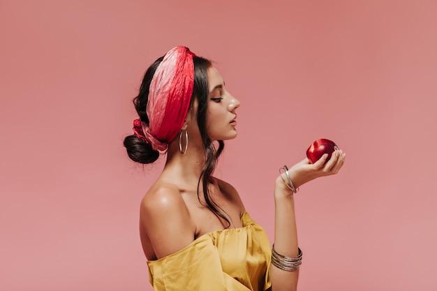 Profielportret van mooi meisje in gradiënthoofdband en toebehoren die rode appel op roze geïsoleerde muur bekijken