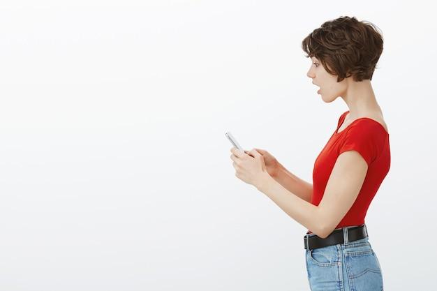 Profielportret van onder de indruk en geschokt vrouw laat kaak vallen terwijl ze naar het smartphonescherm staart