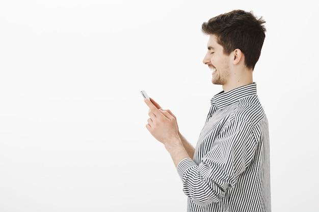 Profielportret van tevreden grijnzende europese mannelijke collega in gestreept overhemd, breed glimlachend op scherm van smartphone terwijl berichten versturen of record van vriend in spel verslaan
