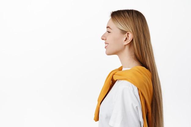 Profielschot van mooie gelukkige vrouw met lang steil blond haar, vrolijk glimlachend, links kijkend naar kopieerruimte, staande in vrijetijdskleding tegen de witte muur
