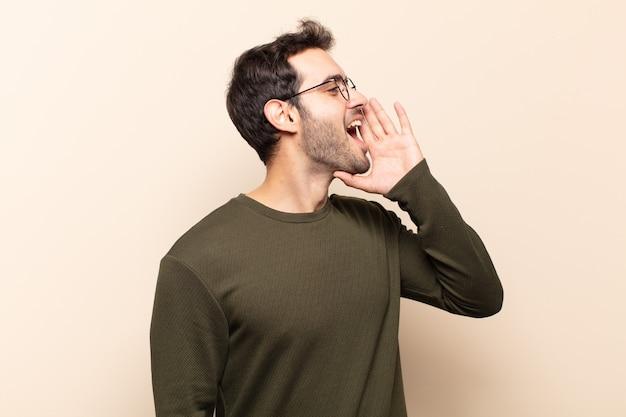 Profielweergave van de jonge knappe man, kijkt blij en opgewonden, schreeuwt en roept om ruimte aan de zijkant te kopiëren