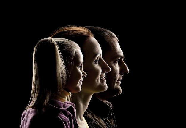 Profielweergave van dochtertje, moeder en vader op zwarte achtergrond