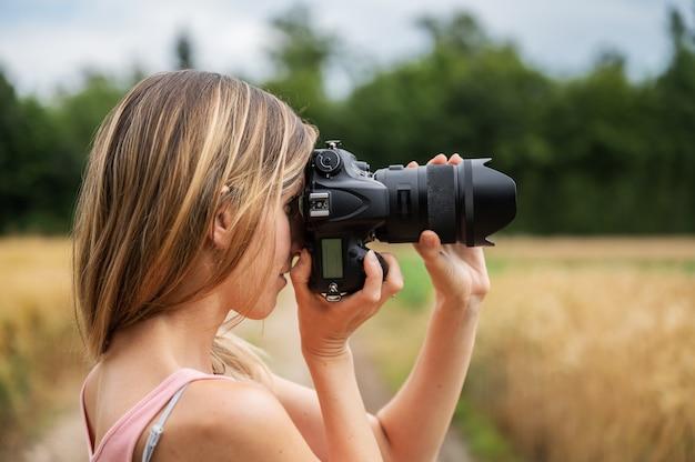 Profielweergave van een jonge vrouw die in de prachtige natuur staat en een foto maakt met een zwarte dslr-camera die het beeld scherpstelt.