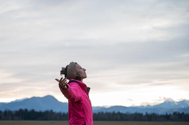 Profielweergave van een jonge vrouw in een roze jas die onder de avondhemel staat met haar armen wijd gespreid en geniet van haar vrede en vrijheid.