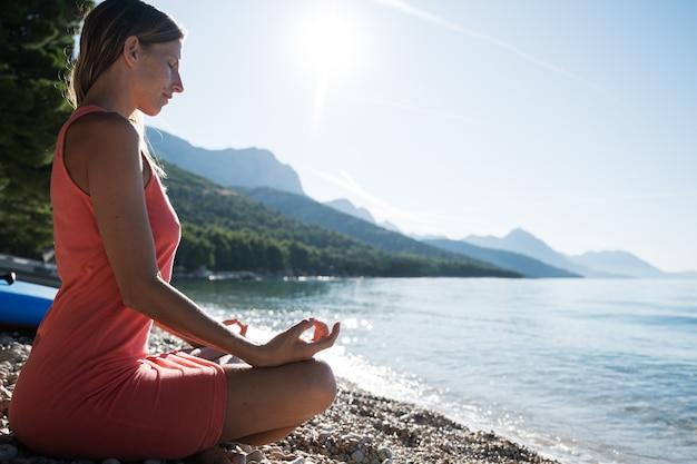 Profielweergave van een jonge vrouw zittend op kiezelstrand in lotuspositie, mediteren door de kalme ochtendzee verlicht door de rijzende zon.