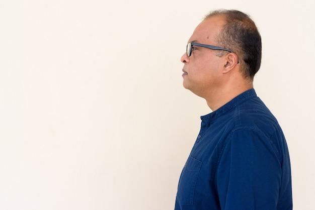 Profielweergave van indiase man tegen gewone muur buitenshuis