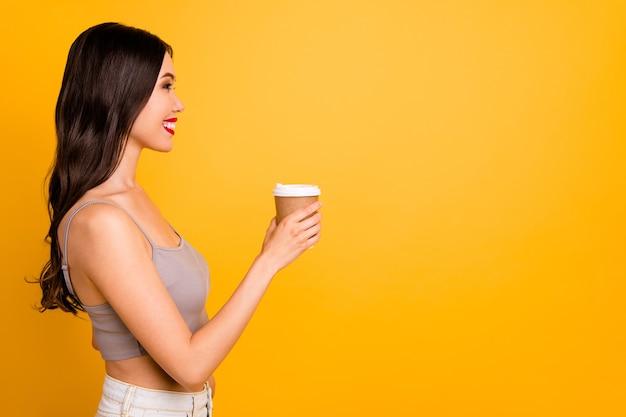 Profielzijde copyspace foto van vrolijke schattig vrij aardige vriendin bedrijf kopje koffie met lippen pomaded op zoek naar lege ruimte reclame thee geïsoleerde levendige kleuren achtergrond