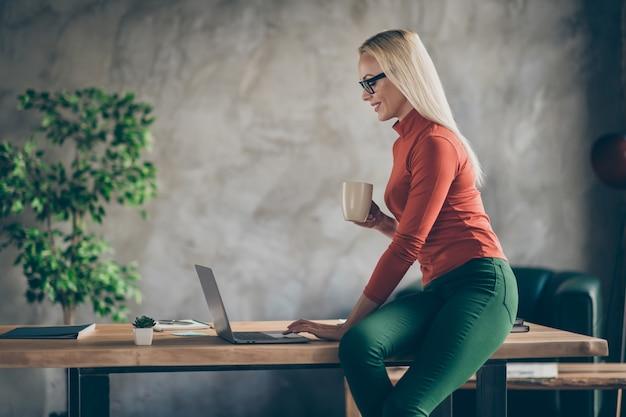 Profielzijde foto van coll slimme deskundige vrouw marketeer zitten bureau houden koffiekopje werken op computer opstartinformatie lezen statistieken op zolder kantoor werkplek dragen rode coltrui Premium Foto