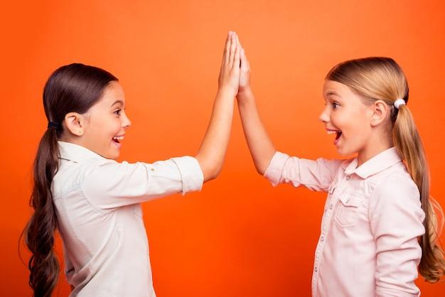 Profielzijde foto van opgetogen positieve vrolijke twee kinderen geven highfive vieren hun wedstrijd winnen overwinning schreeuwen ja draag witte shirts geïsoleerd felle kleur achtergrond