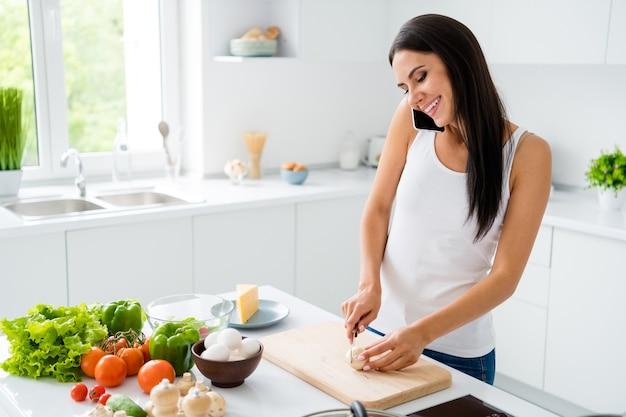 Profielzijde foto van positieve vrolijke meisje huisvrouw hebben rust ontspannen willen lunch bereiden gezondheidszorg avondmaal champignon gesneden op houten snijplank communiceren met vrienden in huis witte keuken
