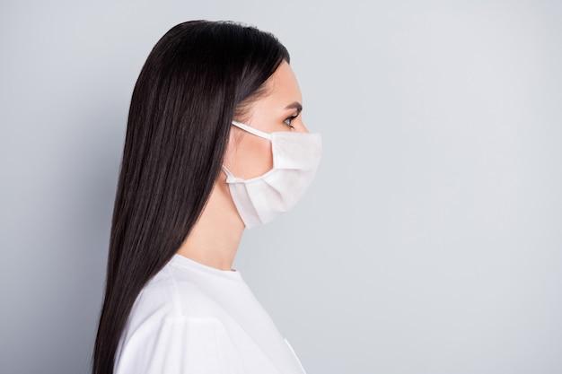 Profielzijde foto van streng meisje in medisch masker kijken copyspace hebben zelfisolatie niet krijgen coronavirus ziek draag stijlvolle kleding geïsoleerd over grijze kleur achtergrond