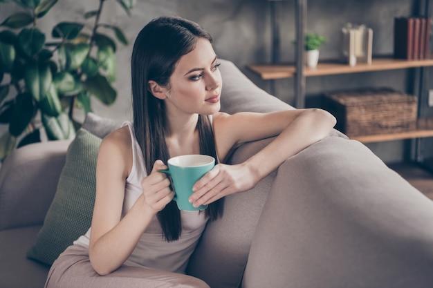 Profielzijde kalm rustig meisje houdt smakelijke koffiekopje droom
