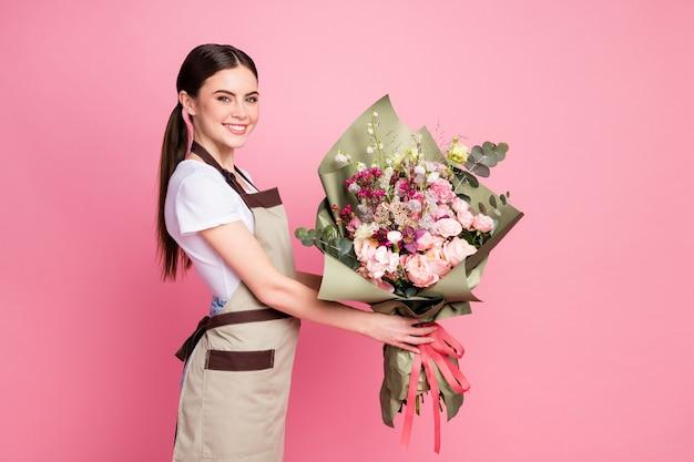 Profielzijportret van een vrolijk meisje dat een bos biologische bloemen geeft