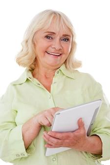 Profiteren van het digitale tijdperk. vrolijke senior vrouw die digitale tablet gebruikt en glimlacht terwijl ze op een witte achtergrond staat